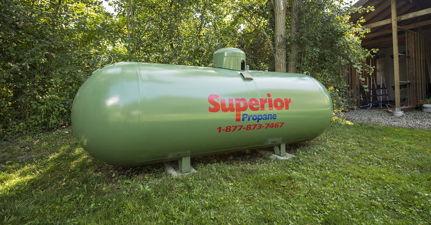 Superior Propane tank next to a shed in a residential backyard.